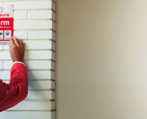 Installatør monterer alarmskilt